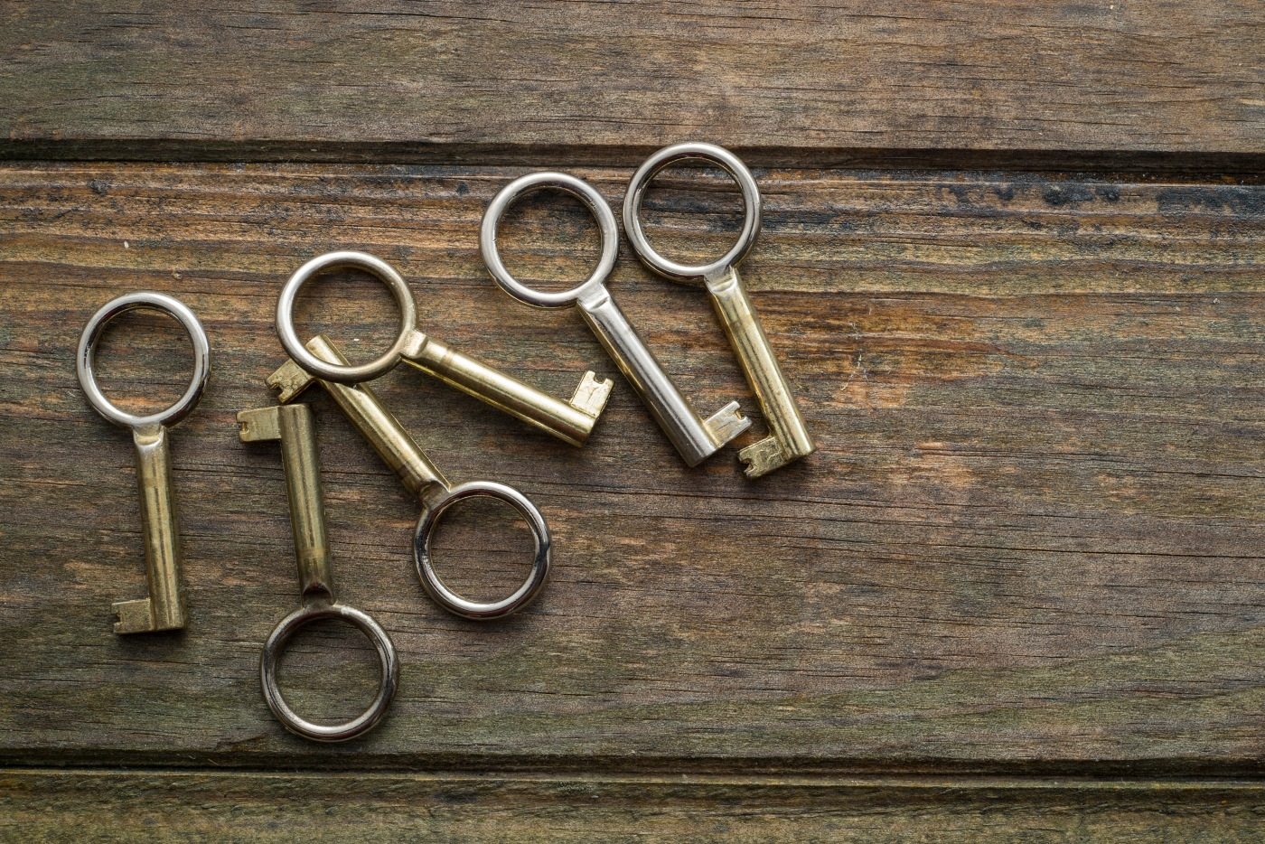 Six golden keys on a wooden background. Copy space